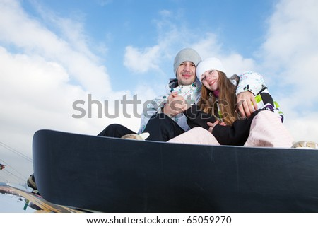 Happy couple on snowboards at winter