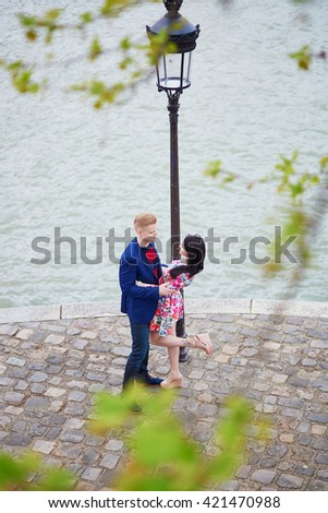 Happy couple on the bank of the Seine in Paris. Tourists enjoying their vacation in France. Romantic date or traveling couple concept - stock photo