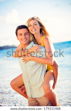 Happy couple on the beach at sunset