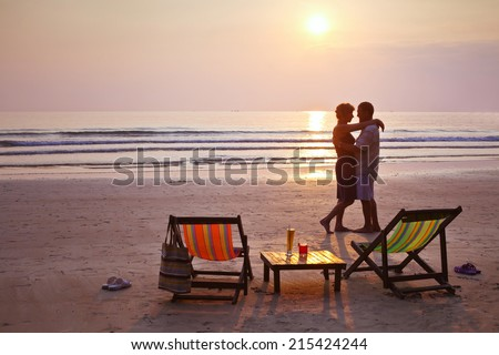 happy couple on the beach at sunset, with deckchairs and cocktails, silhouettes