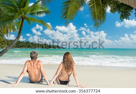 Happy couple on the beach at tropical resort  - stock photo