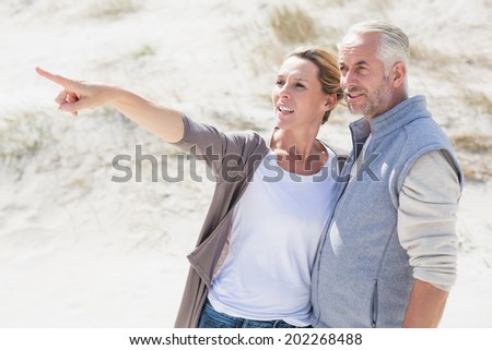 Happy couple on the beach looking at something on a bright but cool day - stock photo