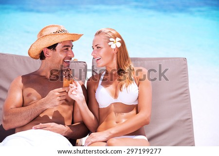 Happy couple on the beach sitting on sunbed and eating tasty sweet ice cream, with love looking on each other, enjoying romantic summer vacation