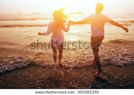 happy couple on the beach, summer vacations or honeymoon - stock photo