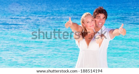 Happy couple on the beach, young family in love spending honeymoon vacation on luxury islands, cheerful active young people having fun at summertime travels, joy of life concept - stock photo