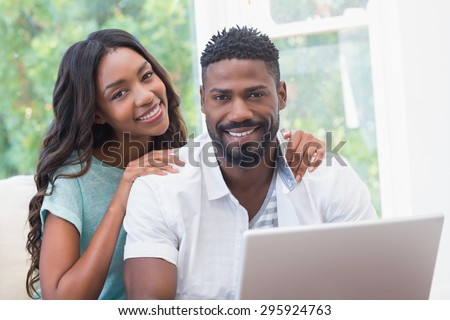 Happy couple on the couch using laptop at home in the living room