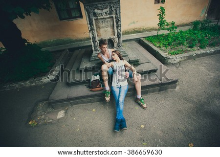 happy couple on the stone steps, a beautiful girl with long dark hair is lying on her boyfriend's knees, love story photo