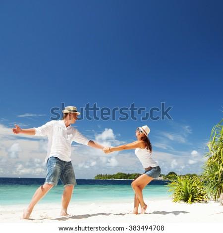 Happy couple on the tropical beach - stock photo