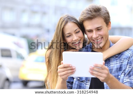 Happy couple or friends hugging and sharing a tablet in the street - stock photo
