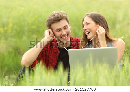 Happy couple or friends sharing music from a laptop sitting in a green field and looking each other - stock photo