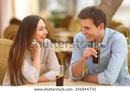 Happy couple or friends talking in a restaurant and looking each other - stock photo