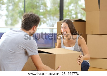 Happy couple or marriage lifting box moving home - stock photo