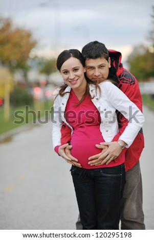 happy couple outdoor,  beautiful pregnant woman with her husband
