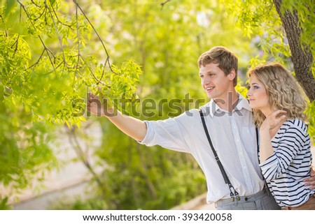 Happy Couple Outdoor. Smiling Couple Relaxing in a Park. Family over Nature Green Background - stock photo