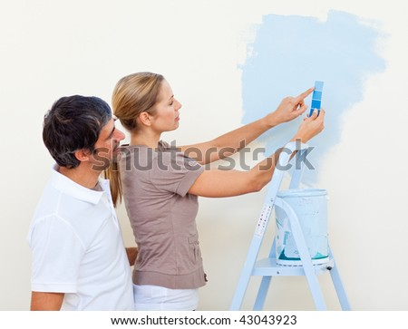 Happy couple painting together in their new house