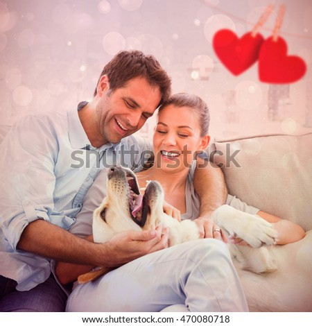 Happy couple petting their yellow labrador on the couch against hearts on line