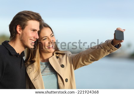Happy couple photographing a selfie with the smart phone outdoors in winter - stock photo