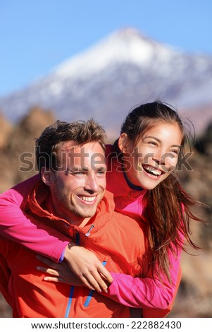 Happy couple piggyback in active lifestyle having fun on hike. Fresh young joyful interracial couple. Asian woman hiker and Caucasian man in outdoor activity on Teide, Tenerife, Canary Islands, Spain - stock photo