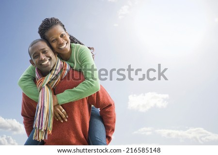 Happy couple piggybacking - stock photo