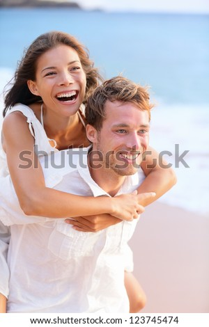 Happy couple piggybacking on beach having playful fun together during summer beach holidays. Cheerful young multiracial couple, Asian woman and Caucasian man in their twenties. - stock photo