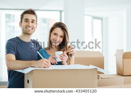 Happy couple planning and designing their new house surrounded by carton boxes, he is drawing on a project - stock photo