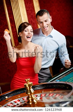 Happy couple playing roulette wins at the casino club - stock photo
