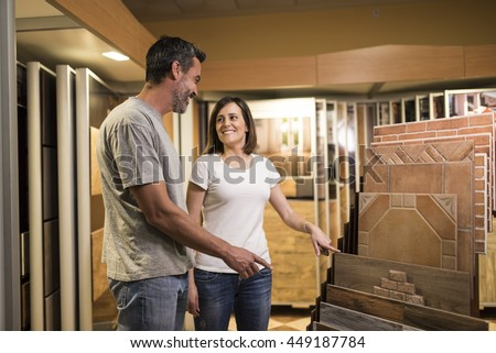 Happy couple pointing at ceramic tile for bathroom floor in store