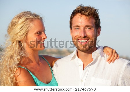Happy couple portrait. Beautiful young caucasian adults in love walking on sunset beach.