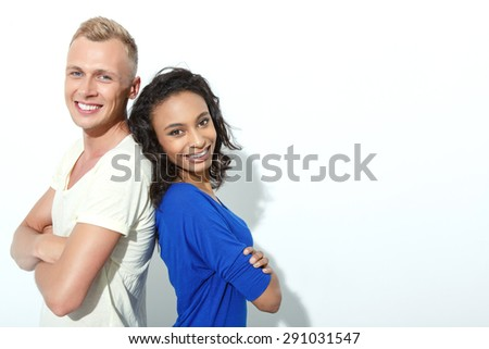 Happy couple. Portrait of a blond young man and his beautiful mulatto girlfriend standing back to back with arms crossed smiling, isolated on white background, copy space