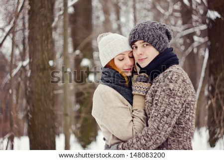 Happy couple posing in cold winter weather in park