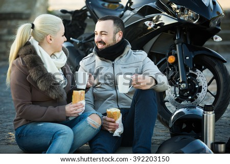 happy couple posing near motor bike with sandwitches and coffee - stock photo