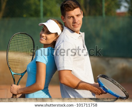 Happy couple posing on tennis court, smiling. - stock photo