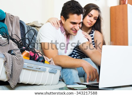 Happy couple preparing for honeymoon and making planning list - stock photo
