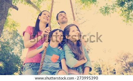 Happy couple pushing kids on swing in playground - stock photo