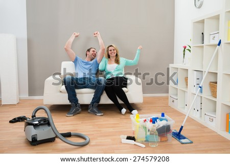 Happy Couple Raising Hand On Sofa With Cleaning Supplies On Floor - stock photo