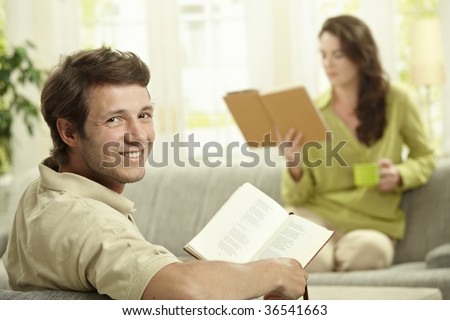 Happy couple reading book sitting at home on couch. Selective focus on man, looking at camera, smiling.