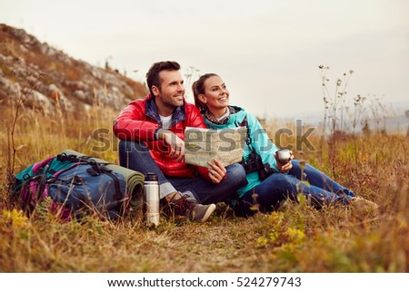 Happy couple reading map and drinking tea during fall, autumn hike