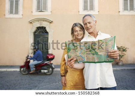 Happy couple reading map on street in Rome; Italy - stock photo