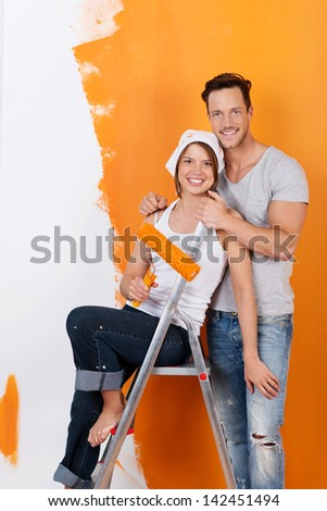 Happy couple redecorating and painting with orange color - stock photo