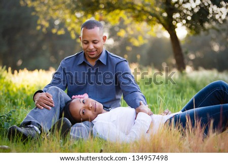 Happy couple relaxing in a grassy field - stock photo