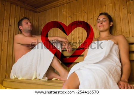 Happy couple relaxing in a sauna against heart - stock photo