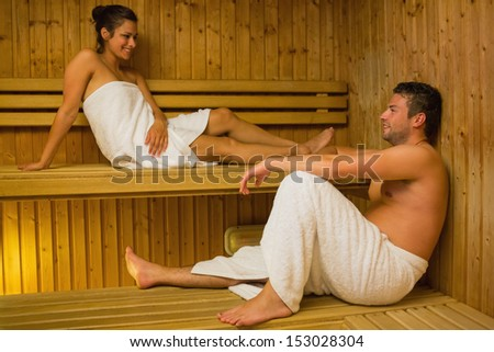 Happy couple relaxing in a sauna and chatting wearing white towels - stock photo