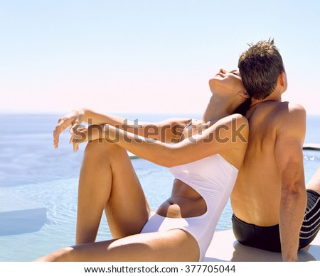Happy couple relaxing in swimming-pool - stock photo