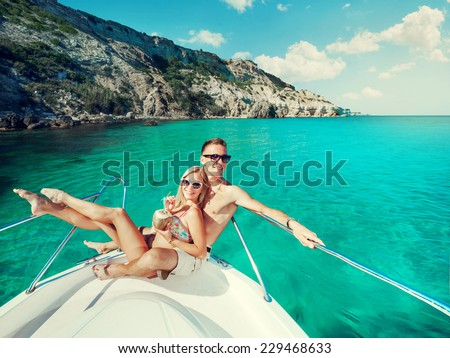 Happy couple relaxing on a boat at sea. Luxury holiday on a yacht.