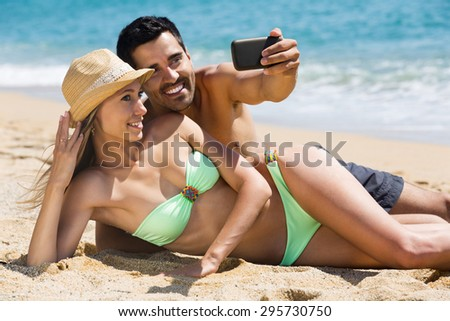 happy couple relaxing on beach taking selfie picture with camera smartphone