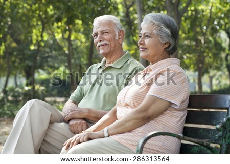 Happy couple relaxing on park bench - stock photo