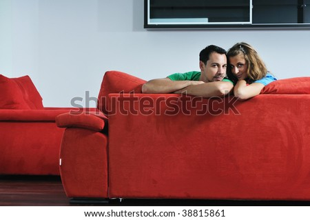 happy couple relaxing on red sofa in big bright new apartment - stock photo