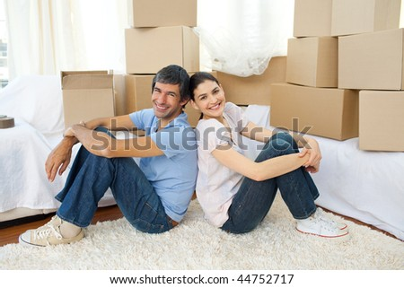 Happy couple relaxing sitting on the floor while moving house