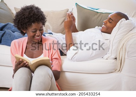 Happy couple relaxing together reading book and using smartphone at home in the living room