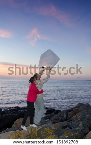 Happy couple release the sky lantern on sea coast